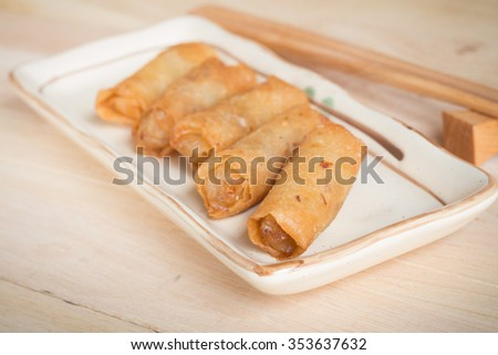 Deep fried spring rolls with pork stuffed serve on wood table that found in East Asian and Southeast Asian cuisine.(soft focus) - stock photo