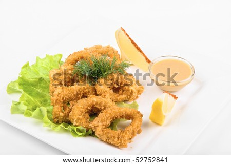 Deep-fried squid with salad leaves, sauce, green and lemon on a white background - stock photo