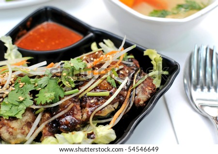 Deep fried tasty meat topped with healthy salad. Suitable for food and beverage, healthy lifestyle, and diet and nutrition. - stock photo