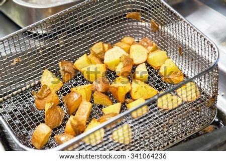 deep fryer with fried potato closeup  - stock photo