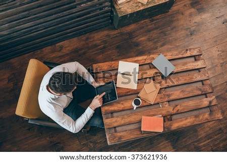 Deep in his work. Top view of young man working on touchpad while sitting at his working place - stock photo