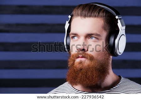 Deep in music. Confident young bearded man in headphones standing against stripped background and listening to the music - stock photo