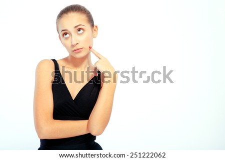 Deep in thoughts. Portrait of beautiful elegant woman in black ballet dress touching her chic with finger and looking up while standing isolated on white background - stock photo
