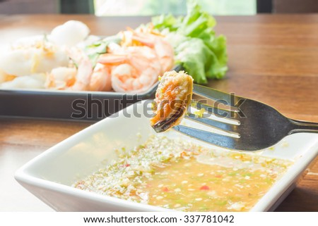 deep mussels fried with fork on sea food sauce, Thai food - stock photo