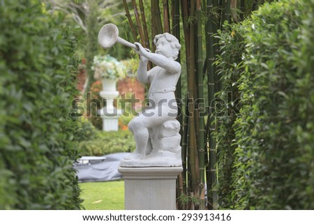 Deep of Cupid Sculpture in garden. - stock photo