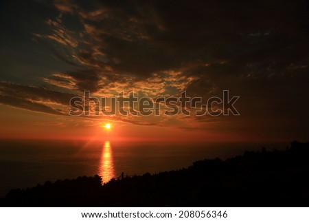 Deep orange sun with reflection on surface of the sea