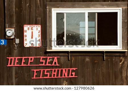 Deep Sea Fishing sign on Prince Edward Island oceanshore - stock photo