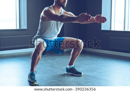 Deep squat. Part of young man in sportswear doing squat at gym - stock photo