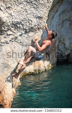 Deep water soloing, male rock climber on cliff - stock photo