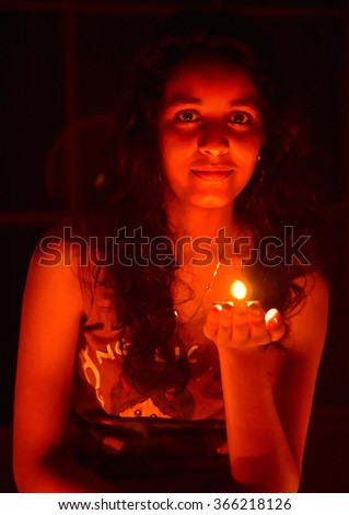 Deepavali, a Hindu celebration. Young Indian girl holding a lamp in her left palm. Monochrom effect.