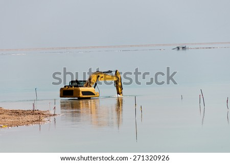 Deepening large bulldozer seabed near the beach on the Dead Sea - stock photo