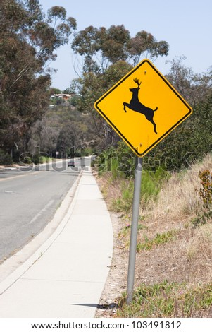 deer crossing warning sign with curve of the road - stock photo