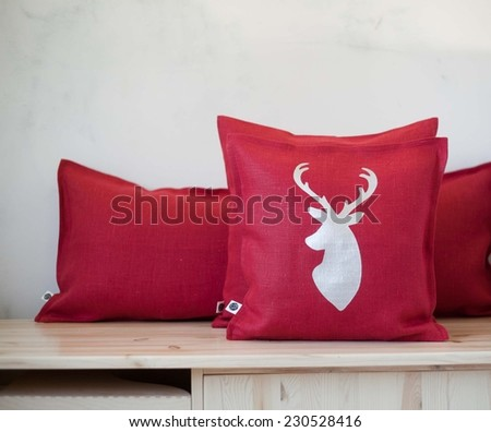 Deer head  on red pillow background in interior - stock photo