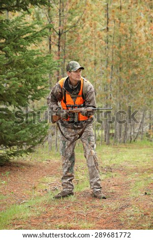 deer hunter stalking in forest - stock photo