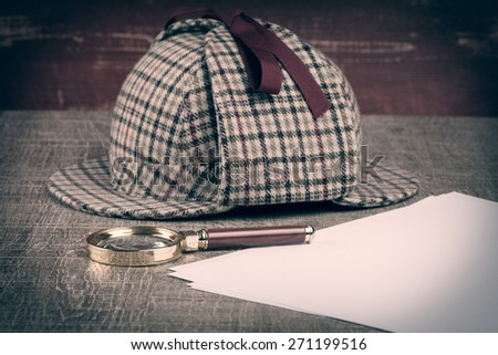 Deerstalker or Sherlock Hat and magnifying glass on Old Wooden table.