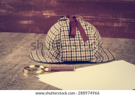 Deerstalker or Sherlock Hat and magnifying glass on Old Wooden table. - stock photo