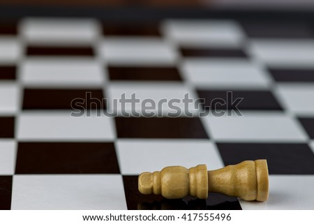 Defeated king chess piece horizontal on chessboard
