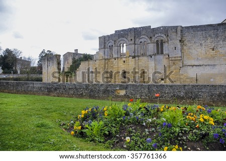 Defence walls and buildings of old medieval village of Saint Emilion with blooming flowers and lawn in Gironde, France.