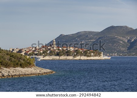 Defended medieval dalmatian town Korcula on the island of Korcula and mountains on Peljesac peninsula in background, Croatia - stock photo