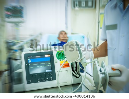 Defibrillation is a treatment for life-threatening cardiac dysrhythmias.Defibrillation consists of delivering a therapeutic dose of electrical current to the heart with a device call a defibrillator - stock photo