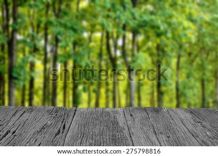 Defocus and blur image of old wood and beautiful green forest for background usage - stock photo