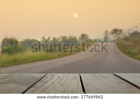 Defocus and blur image of terrace wood and asphalt road through the west in sunset time for background usage - stock photo