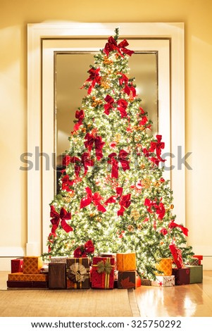 defocus blured of beautiful Christmas tree and gifts in golden room , photo in vintage tone