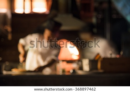 defocus blurred photo of chef working cook some delicious food with exterior kitchen background - stock photo