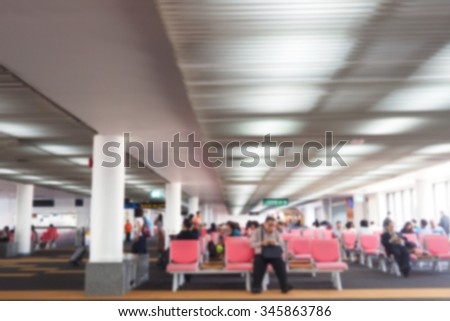 Defocus blurred picture of travellers, passengers waiting for their flight at airport - stock photo