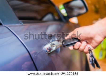 Defocus photo Male hand pressing on the remote control car alarm systems - stock photo