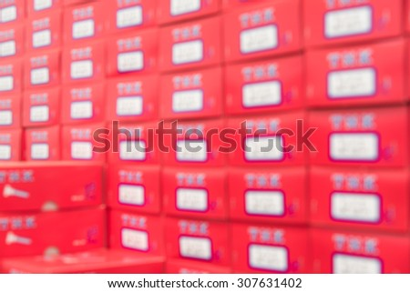 Defocused a stack of red boxes on shelves for product packaging inside factory warehouse - stock photo