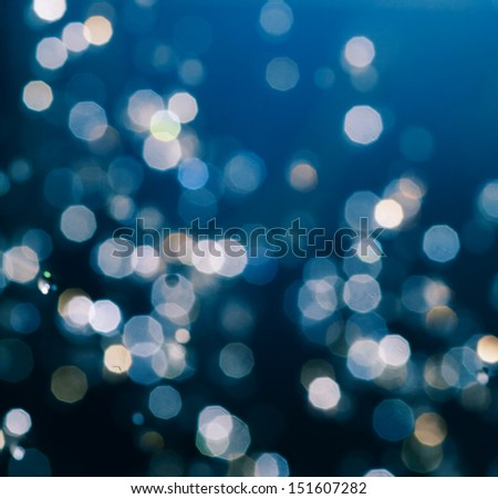 Defocused abstract bokeh blue christmas background. Xmas is coming with snow in winter - stock photo