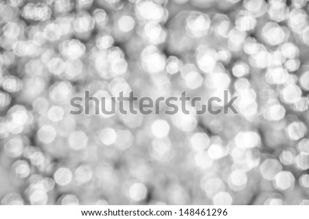 Defocused abstract silver bokeh against a dark background for use at graphic design - stock photo