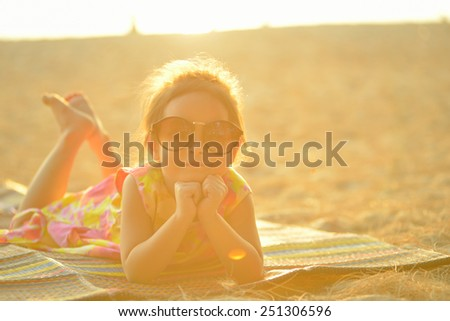 Defocused and blurred image Child kid posing and fun on the beach with golden light at sunset summer - stock photo