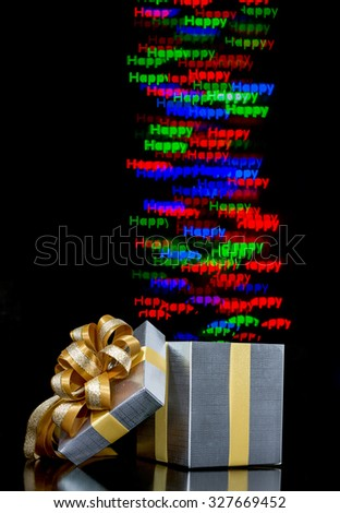 Defocused bokeh lights happy word are moving out of open gift box - stock photo