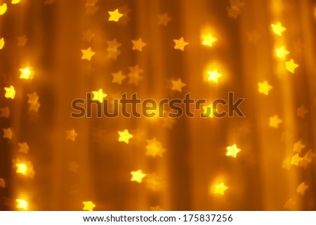 defocused golden lights in the shape of stars - stock photo