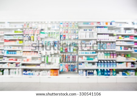 Defocused image of medicines arranged in shelves at pharmacy - stock photo