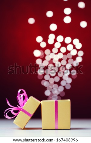 Defocused lights are moving out of open gift box - stock photo