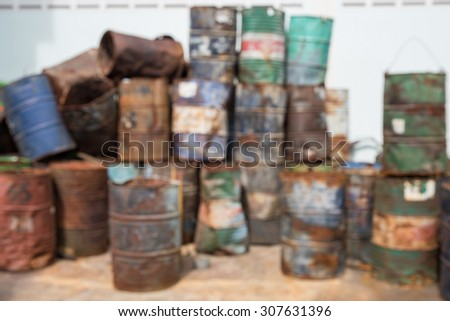 Defocused oil or gasoline containers/tank in a rusty and old condition - stock photo