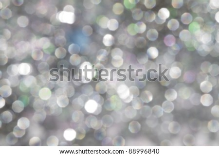 defocused silver bokeh background with green, pink and blue lights