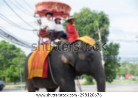 Defocused tourists on an elephant in AYUTTHAYA, THAILAND