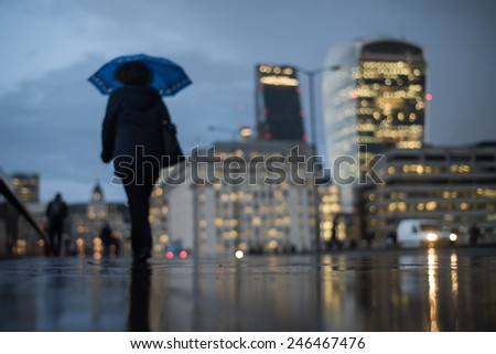 Defocused view of the City of London with a woman walking under the umbrella on a rainy day. Skyline includes 20 Fenchurch St and 122 Leadenhall St.