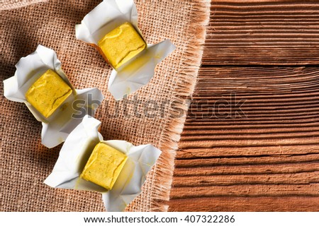Dehydrated condiment bouillon stock cube salty meat and vegetables aromatic yellow spice, ingredient single whole portion wrapped and open in paper pack , view from above. - stock photo