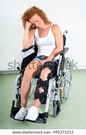 Dejected disabled young woman in a wheelchair with her leg in a brace following knee surgery sitting staring sadly at the floor