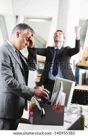 Dejected fired office worker. His colleague is celebrating on the background - stock photo