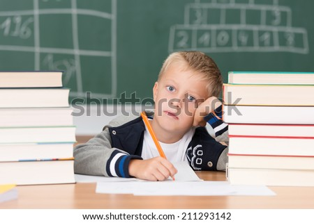 Dejected little boy in class in school sitting at his desk between two tall stacks of text books working on his notes - stock photo