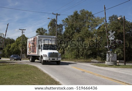 DeLand Florida USA - October 2016 - Delivery truck crossing a railroad track at DeLand Station