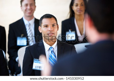 Delegates Listening To Speaker At Conference - stock photo