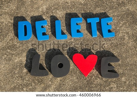 Delete, and love text on a gray concrete background. - stock photo