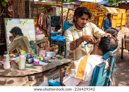 DELHI - APR 16: Barber working in his small shop on April 16, 2011 in Delhi, India. Delhi is the largest urban agglomeration in India by population, and the 4th most populous city on the planet. - stock photo